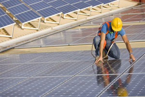 photo of man with yellow hard hat and harness kneeling down on photovoltaic arrays